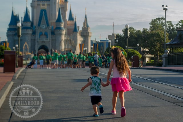 Bella and Jackson walking up Main Street USA to Cinderella Castle in the Magic Kingdom