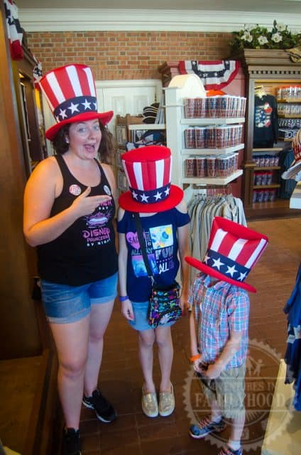 Kids try on Uncle Sam top hats at American Adventure in Epcot World Showcase