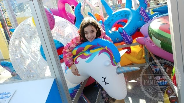 Bella Finds a giant inflatable unicorn to hug outside Toy Fair NY 2018