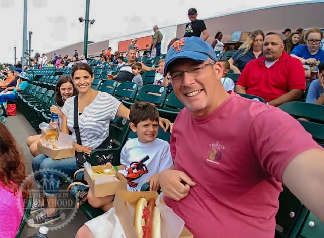 The whole family enjoying a day at the ballpark to watch a baseball game