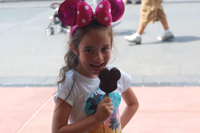 Bella is about to take the first bite of her Mickey Premium Ice Cream Bar while wearing her pink sparkly Minnie ears.