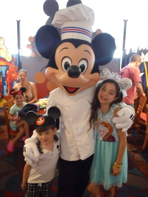 Jackson and Bella get their picture taken with Chef Mickey in his white coat and chef's hat
