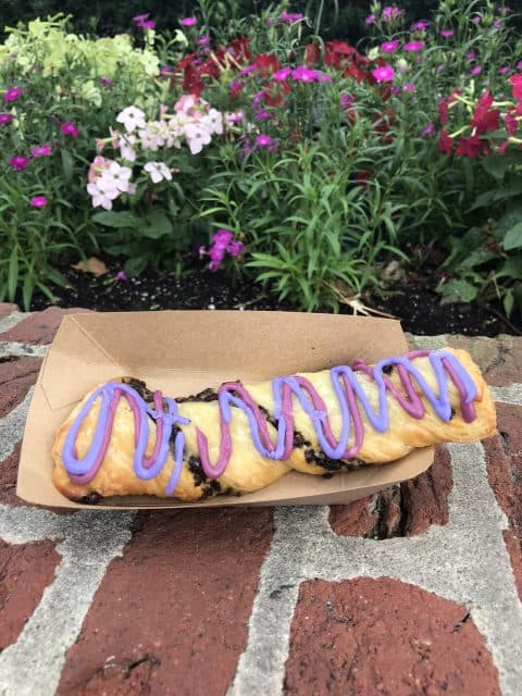 A Cheshire Cat Tail pastry in its container on a brick ledge in front of a flower bed