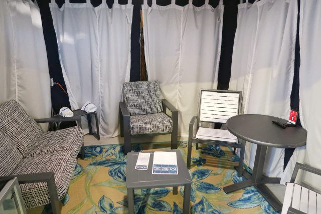 a look inside the cabanas at the Kartrite indoor water park. Several chairs, a loveseat, table, and small refrigerator are seen.