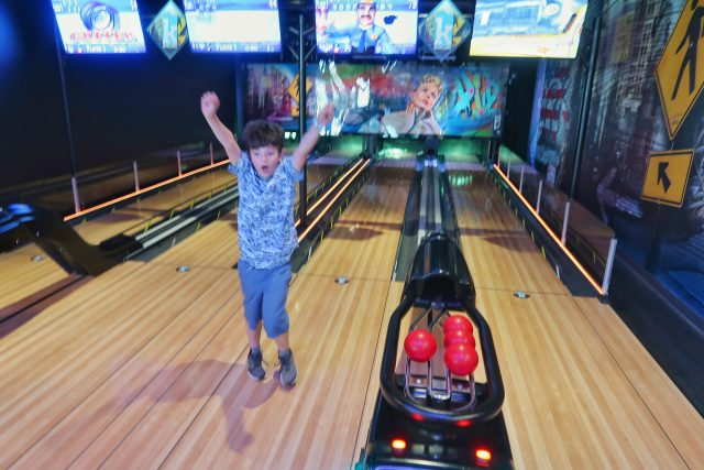 jackson raises his arms to celebrate bowling a strike at the Kartrite Resort arcade