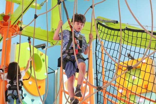 Jackson climbs across a rope bridge suspended high above the ground. He is wearing a harness for safety.