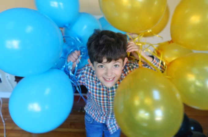 Jackson with two bunches of balloons, one blue, one gold.