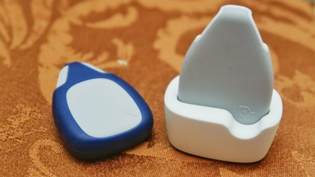 two jiobit location monitor devices on table, one in its charging dock