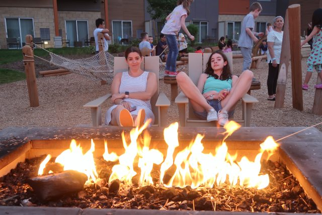 Lisa and Bella relax and enjoy the fire pit outside at the Kartrite Resort while kids play in the background.