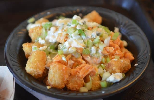 Tater tots in a bowl, topped with shredded buffalo chicken, blue cheese, and chopped celery.