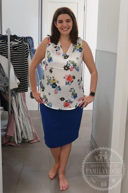 Me trying on a white floral shirt with a blue skirt from Macy's Backstage