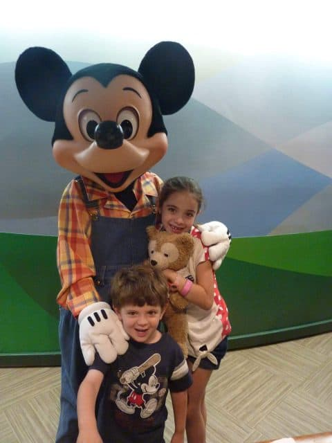 The kids pose with Mickey Mouse in his farmer outfit (Overalls and Plaid shirt) at the Garden Grill in Epcot