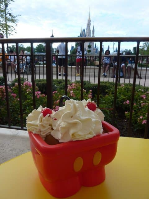 An ice cream sundae in a plastic sink that looks like Mickey Mouse pants sits on a table outside the Plaza Ice Cream Parlor. Cinderella Castle can be seen in the background.