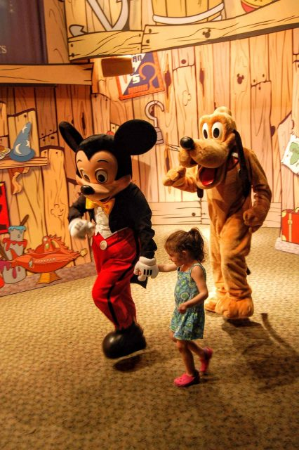 Bella marches with Mickey Mouse and Pluto at the Disney Visa Cardmember Character Experience