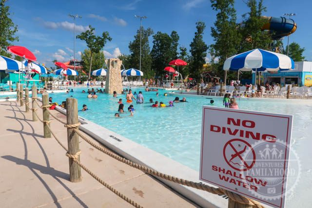 No Diving sign at the new Calyspo Springs activity pool. People can be seen swimming in the background.