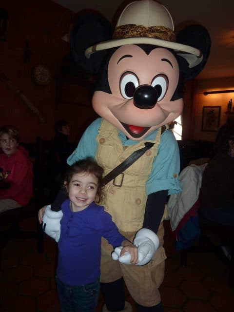 Bella poses with Mickey Mouse in his khaki outfit and safari hat at Tusker House Restaurant