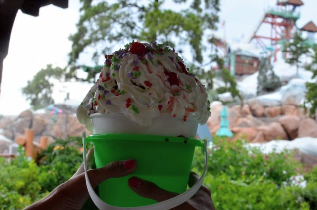 Sand Pail Sundae dripping whipped cream. Blizzard Beach water slides in the background.