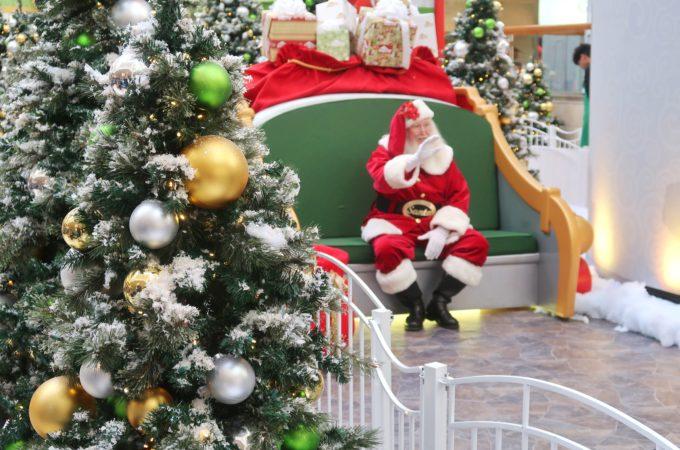 santa waves to a kid from his photo bench at Santa HQ