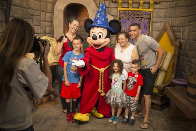 A multi-generational family poses with Sorcer Mickey Mouse at Red Carpet Dreams in Disney's Hollywood Studios