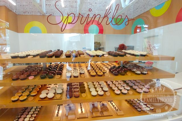 assorted Cupcakes on the shelves behind glass at Sprinkles