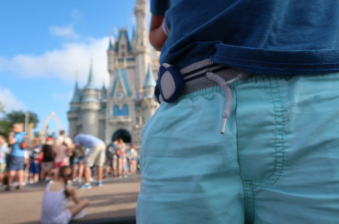 closeup of jiobit clipped to waistband with cinderella castle in background