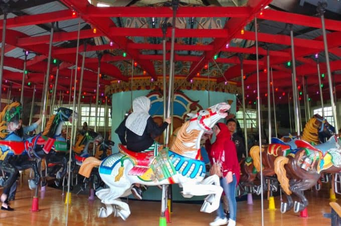 people riding the central park carousel