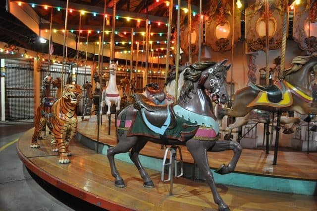 The forest park carousel has horses and menagerie animals like the tiger