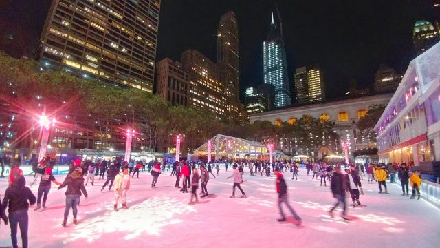 ice skaters on the ice at the rink at Bryant Park at night