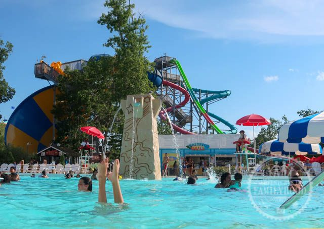 A child's legs stick out of the water as people swim and play in the new Calypso Springs pool at Hurricane Harbor. Large waterslides can be seen in the background.