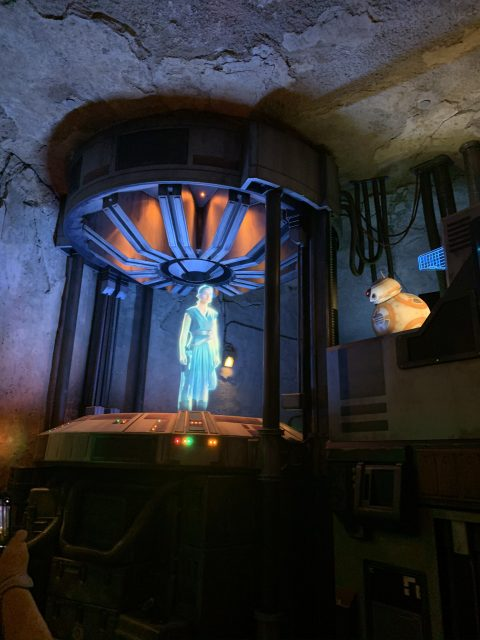 """a Hologram of Rey communicates with BB-8 inside the queue for """"Star Wars: Rise of the Resistance"""""""