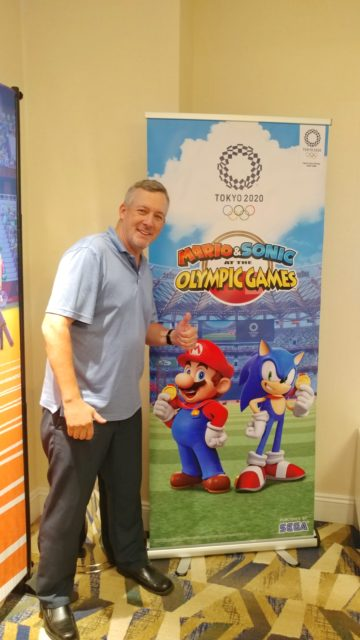 Me giving a thumbs up in front of a sign for Mario & Sonic at the Olympic Games Tokyo 2020