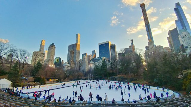 ice skaters at wollman rink with new york city skyline in background